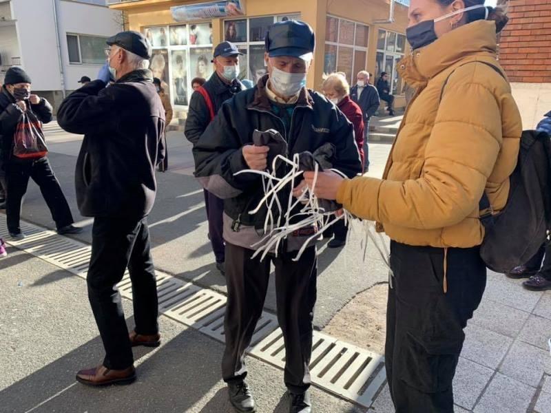 Доброволци раздават маски на възрастните хора, които чакат за изплащенето